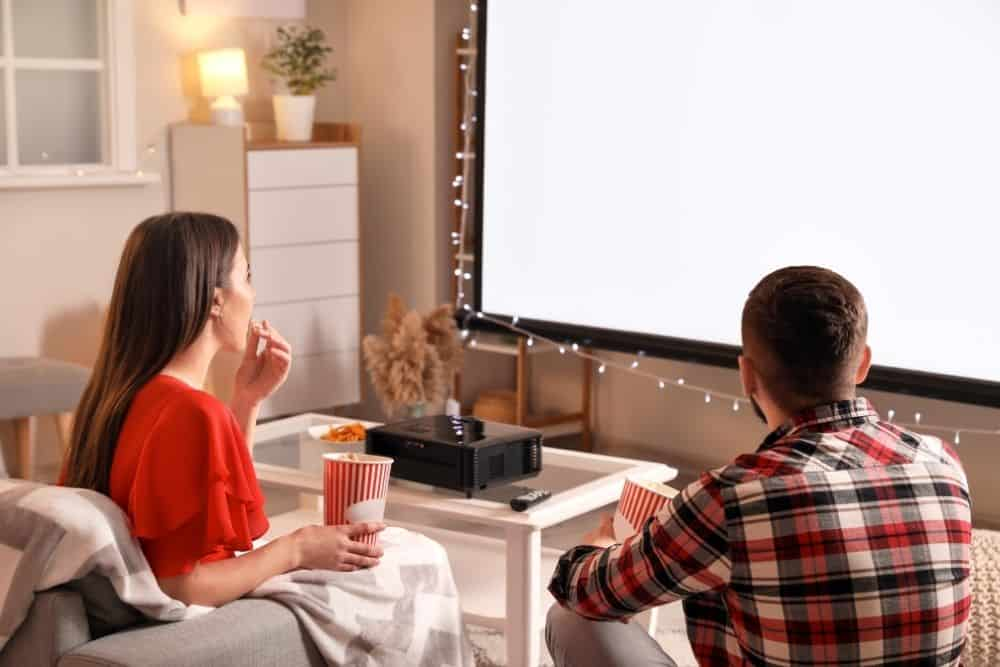 a couple watching movies with a short throw projector
