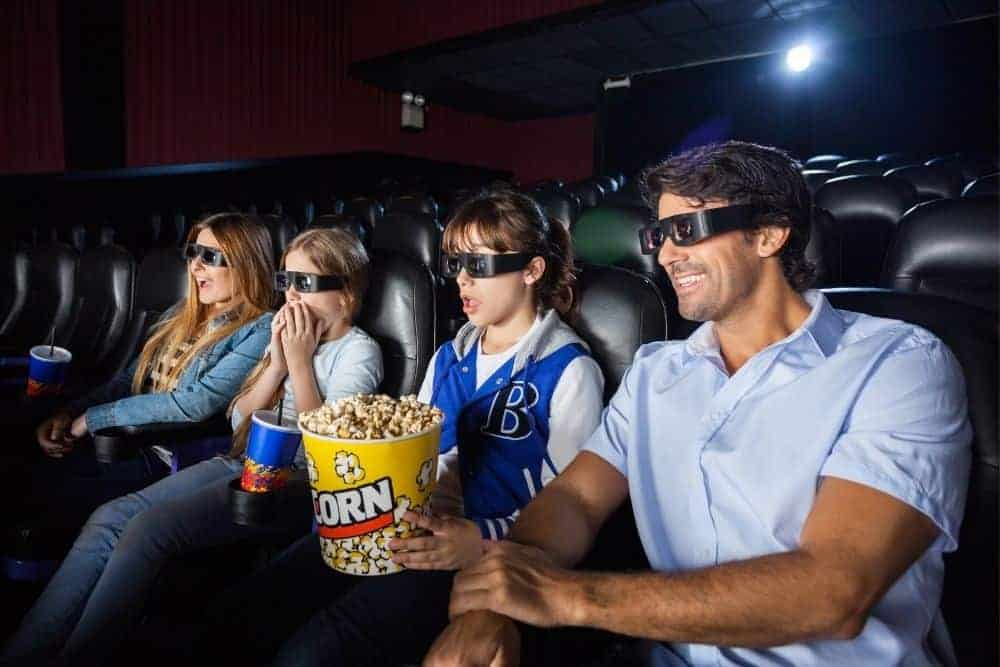a group of friends in a cinema choose seating distance from projector screen with the double-width method