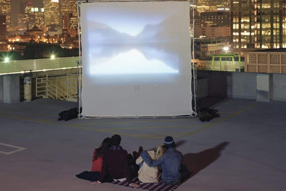 a group of friends using rear projector screens for movie night outdoor on a rooftop