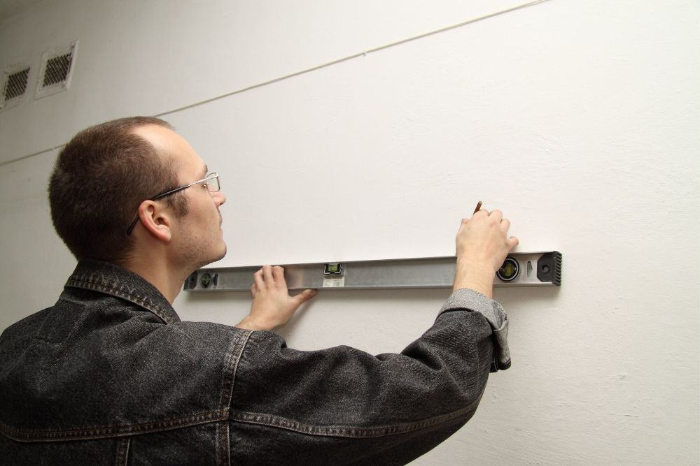 a man measures a wall to mount his projector