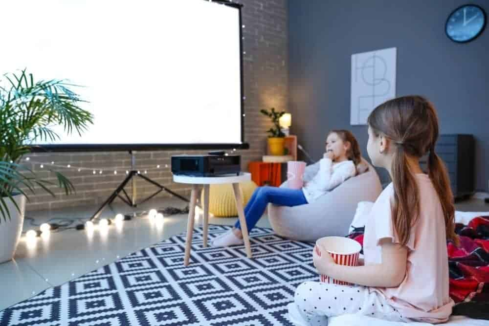 two children sitting in front of a projector screen