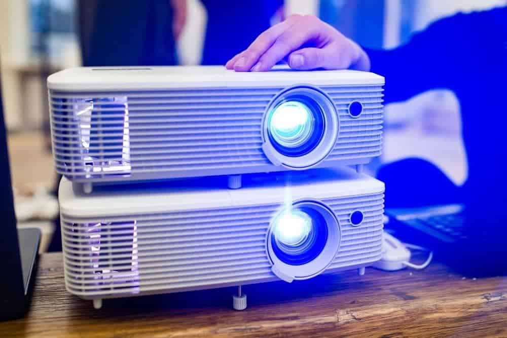 two projectors with blue lamp light