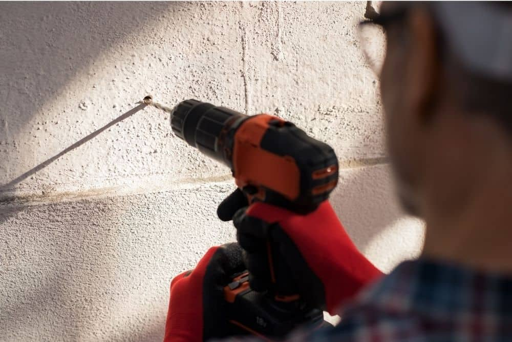 man drilling holes in the wall