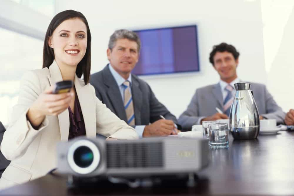 a woman using a projector remote control at a meeting