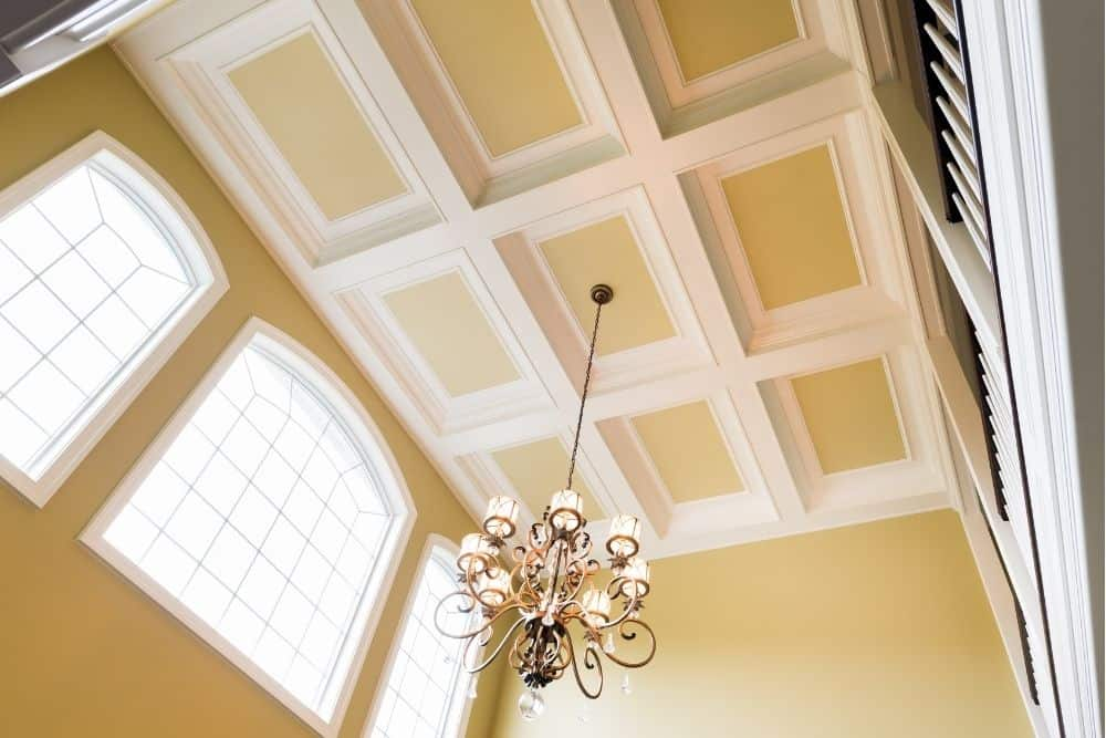 a coffered ceiling holds a chandelier