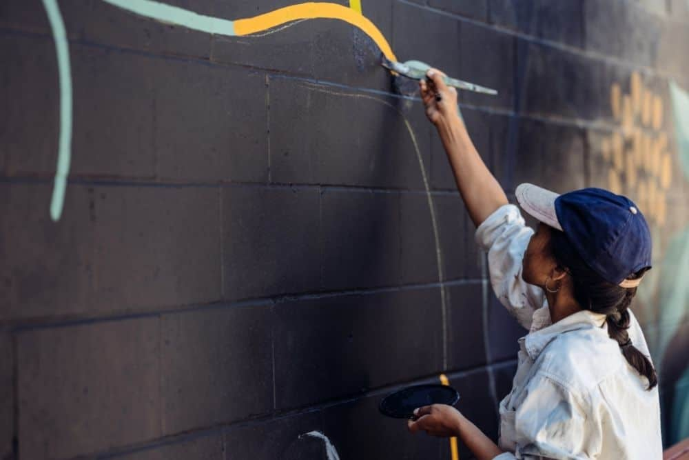 a muralist tracing on the wall