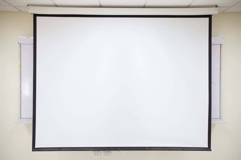 a screen pulled down in front of a white board