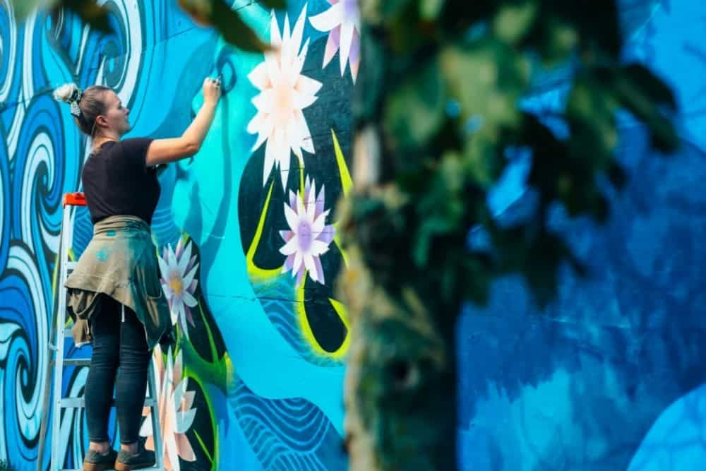 a women painting mural on the wall