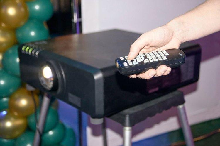 man adjusting projector color via a remote control