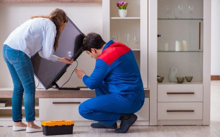 a man repairing a TV