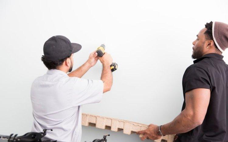 2 men installing a fixed projector screen