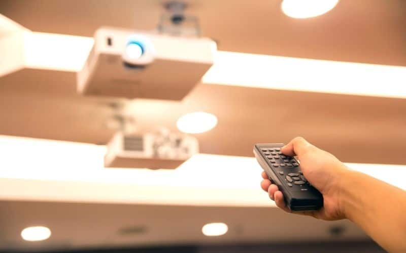 a person using remote to control a ceiling-mounted projector