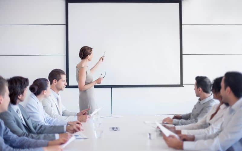 a woman giving a presentation using projector