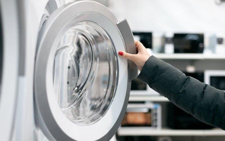 a woman opening a washing machine